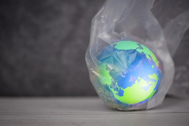 Plastic wereld of wereldmilieudag, de planeet aarde in een plastic zakverbod zegt geen plasticvervuiling nul afval recyclen