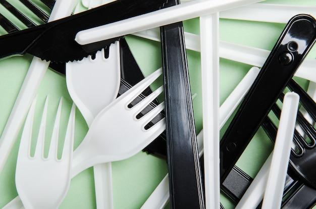 Plastic witte en zwarte vorken en messen op een groene ondergrond