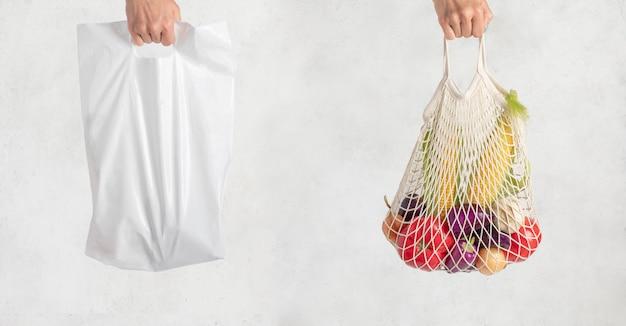 Plastic zak en netje in de hand op een witte. winkelen zonder afval. milieuvriendelijke wegwerpverpakking