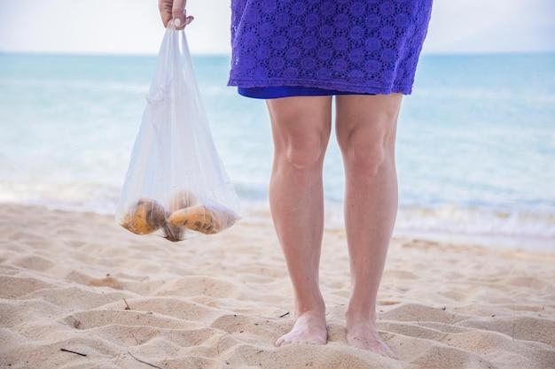 Plastic zak met fruit in de hand van een vrouw op het strand, geen gezicht op het concept van vervuiling van