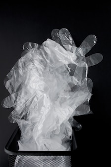 Plastic zak met handvatten, handschoenen in de bak op een zwarte achtergrond. gebruikte plastic zak voor recycling. concept - ecologie, vervuiling van de planeet met plastic cellofaan polyethyleen