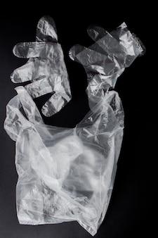 Plastic zak met handvatten, handschoenen, op een zwarte achtergrond. gebruikte plastic zak voor recycling. concept - ecologie, vervuiling van de planeet met plastic cellofaan polyethyleen