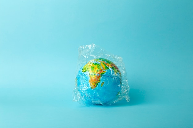 Plastic zak vervuiling concept. earth globe in een plastic zak op een gekleurde achtergrond. plastic en afvalvervuiling oceanen, natuur