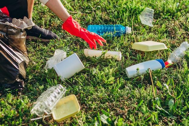 Plastic zakken die in de weide worden gedumpt, besmetten het milieu. stapel plastic en glazen flessen op groen gras in de natuur milieuproblemen. bescherming van de natuur.