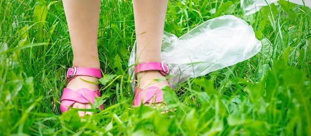 Plastic zakken prullen met kindervoeten op groen gras tijdens het schoonmaken van het park van plastic afval