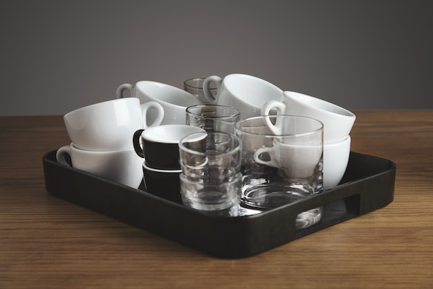 Plastic zwart presenteerblad met schone lege witte koffie, thee, whiskyglazen en kopjes. op dikke houten tafel in caféwinkel. geïsoleerd op grijze achtergrond.