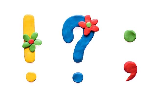 Plasticine gekleurde leestekens: uitroepteken, vraagteken, punt, komma met bloemen, isoleren op witte achtergrond