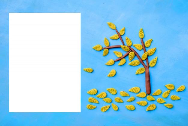 Plasticine gele herfstboom en een wit vel papier