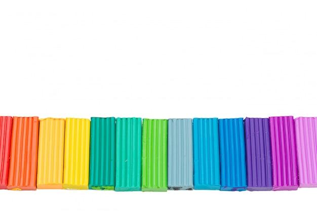 Plasticine kleurrijke stokken die over witte achtergrond worden geïsoleerd
