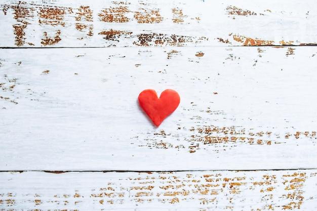 Plasticine rood hart op witte houten achtergrond.