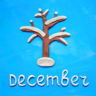 Plasticineboom in de sneeuw en het woord december op blauwe achtergrond