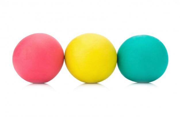 Plasticineklei drie rode geelgroene bal op witte close-up als achtergrond