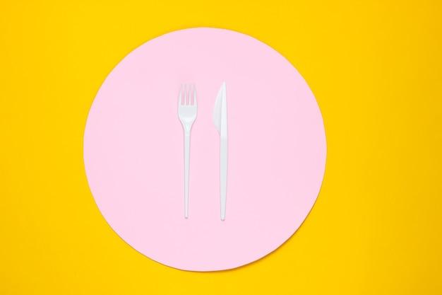Plastick vork en mes op gele achtergrond met roze cirkel. bovenaanzicht, minimalisme