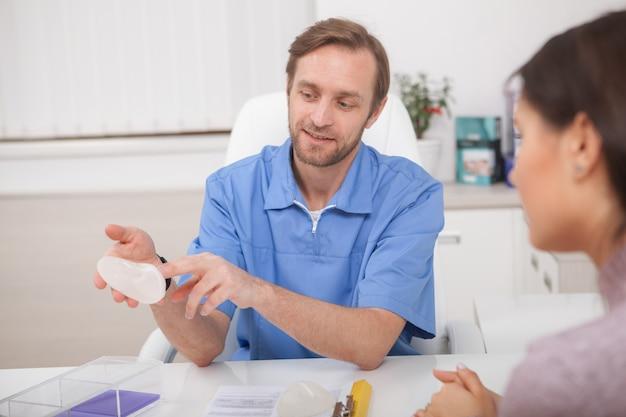 Plastisch chirurg die borstimplantaten toont aan een patiënt