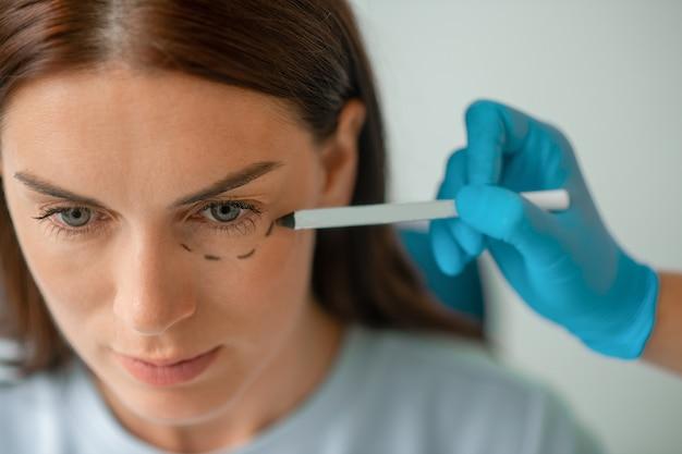 Plastisch chirurg die lijnen trekt op het gezicht van de cliënt