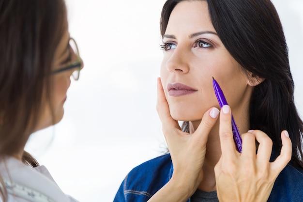 Plastisch chirurg die streepjeslijnen op het gezicht van haar patiënt trekt.