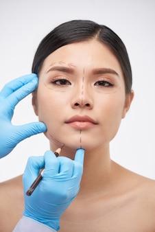 Plastisch chirurg tekening op gezicht