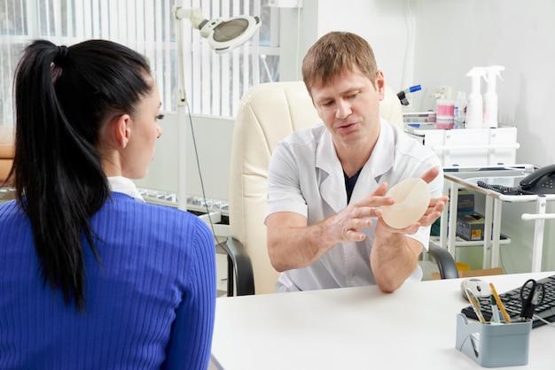 Plastisch of cosmetisch chirurg toont vrouwelijke patiënt borstimplantaat monsters voor haar toekomstige operatie. professionele en beroemde chirurg die werkt in een respectabele kliniek.