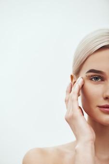 Plastische chirurgie operatie bijgesneden foto van mooie en jonge blonde vrouw die haar gezicht aanraakt met