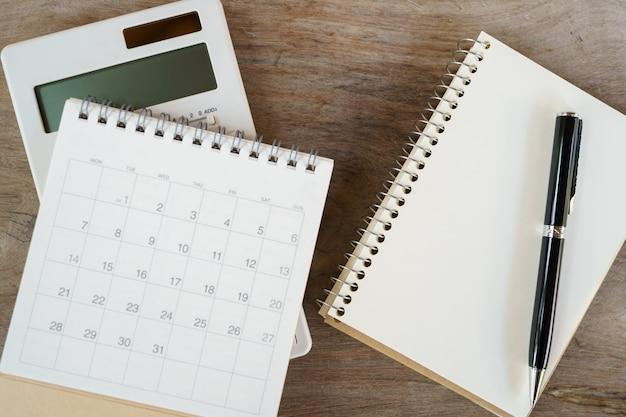Plat bovenaanzicht bureau tafel met lege notebook, smartphones, rekenmachines en andere kantoorbenodigdheden