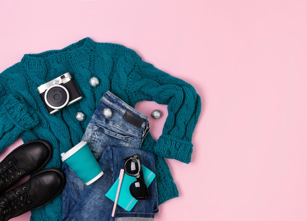 Plat bovenaanzicht vrouwelijke casual look met warme turquoise trui, jeans, laarzen en zonnebril