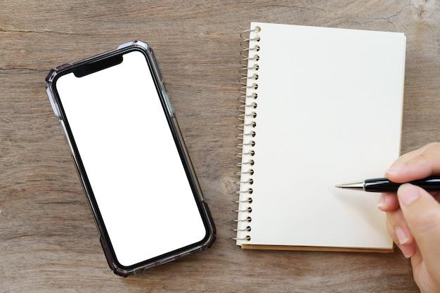 Plat bureau van bovenaanzicht met leeg notitieboekje, smartphones, rekenmachines en andere kantoorbenodigdheden