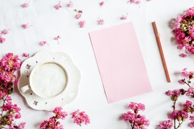 Plat bureaublad items: koffiemok, blanco papier, pen en roze bloemen op witte tafel