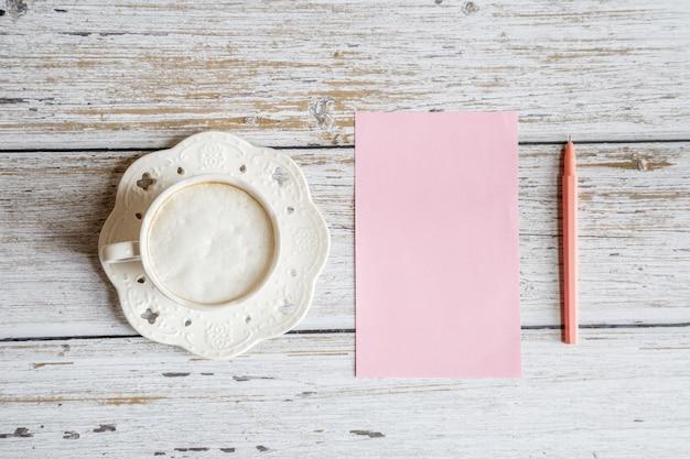 Plat bureaublad items: koffiemok, blanco papier, pen op witte houten tafel
