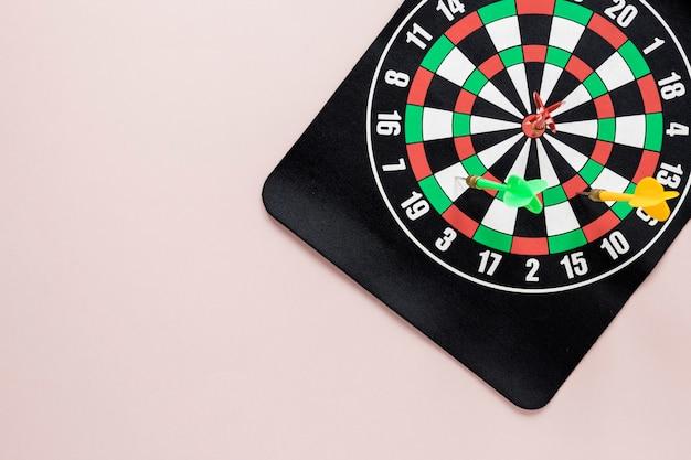 Plat darten tafel op roze achtergrond met kopie ruimte