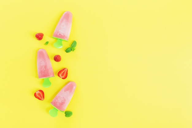Plat gelegd met fruitig roze bevroren sorbetijs op groene plastic stokcollectie met stukjes aardbei, muntblaadjes op gele achtergrond. bevroren gemengd fruit met yoghurt in de vorm van ijs