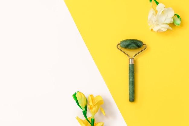 Plat gelegd met groene jaderoller en bloemen op gele en witte achtergrond en kopieerruimte