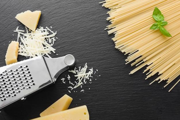 Plat geraspte parmezaanse kaas en rasp met ongekookte spaghetti