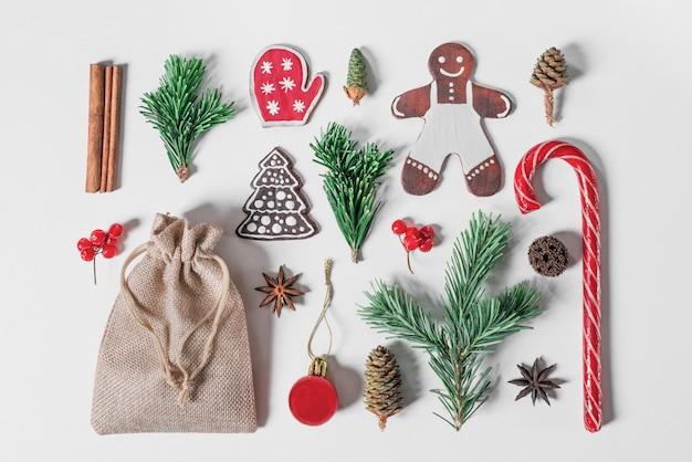 Plat kerstmis samenstelling met peperkoek snoepjes, fir brunch en dennenappels.