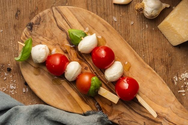 Plat kerstomaatjes en spiesjes van mozzarella leggen
