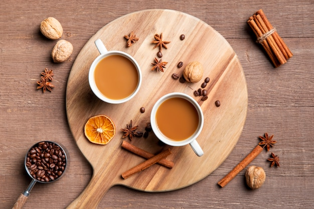 Plat koffie kopjes op een houten bord met ingrediënten