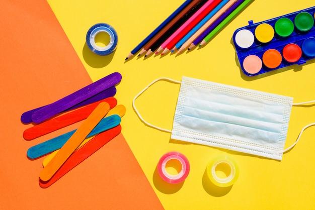 Plat lag achtergrond met het concept van terug naar school beschermd met sanitaire maskers.