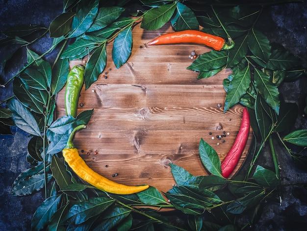 Plat lag achtergrond met verse laurus bladeren en chili peper op houten snijplank.