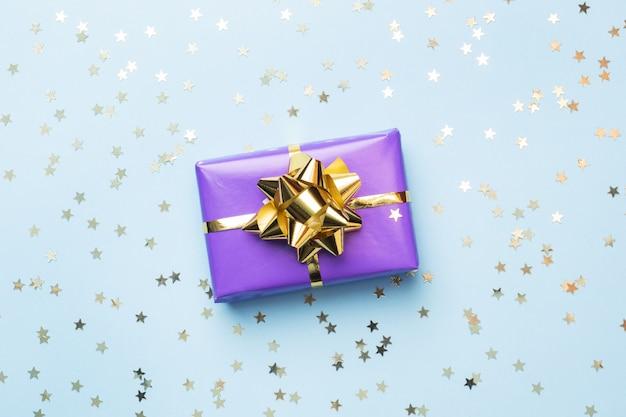 Plat lag achtergrond voor feest kerstmis en nieuwjaar. geschenkdozen zijn paars met gouden linten strikken en confetti sterren op een blauwe achtergrond. bovenaanzicht kopie ruimte.