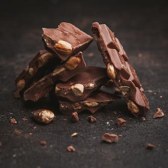 Plat lag amandelen met chocolade op donkerbruin getextureerd.