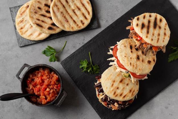 Plat lag arepa's met vlees en tomaten