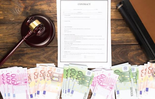 Plat lag arrangement met bankbiljetten, boek, contract en hamer