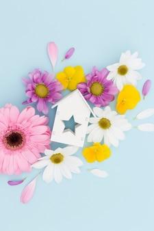 Plat lag arrangement met bloemen en houten huis