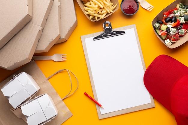 Plat lag arrangement met eten en klembord