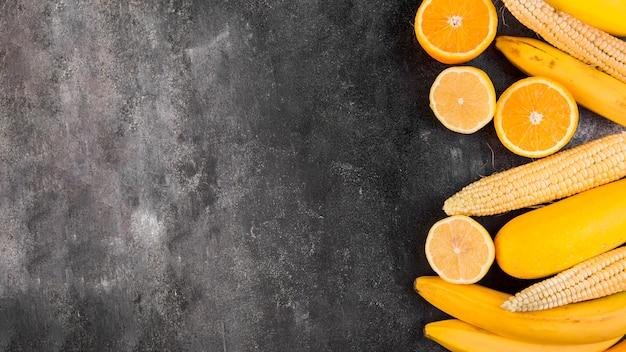 Plat lag arrangement van maïs en sinaasappels met kopie ruimte