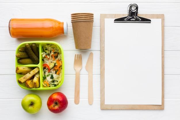 Plat lag arrangement van verschillende voedingsmiddelen met een leeg klembord
