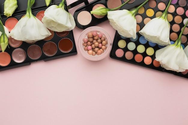 Plat lag assortiment met make-up paletten en bloemen
