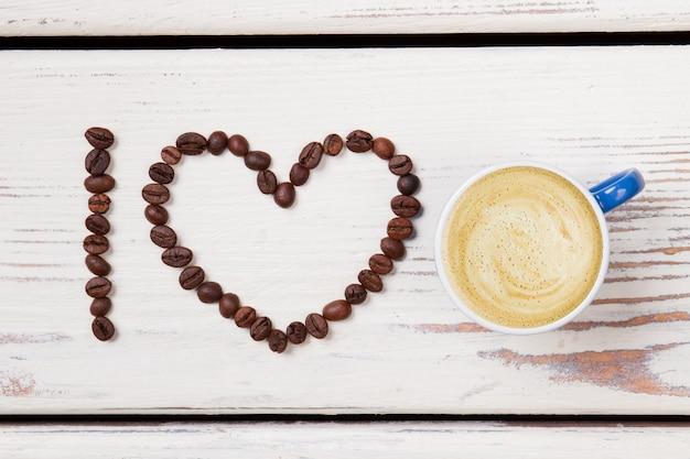 Plat lag blauwe kop koffie en bonen gerangschikt in een hart. ik hou van koffie. wit houten oppervlak.