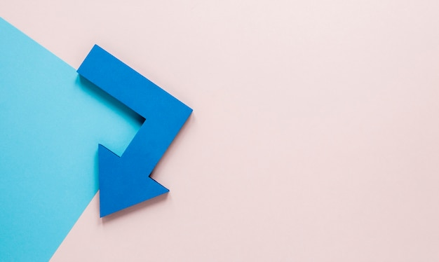 Plat lag blauwe pijlen en blauwe kartonnen mock-up op roze achtergrond met kopie-ruimte