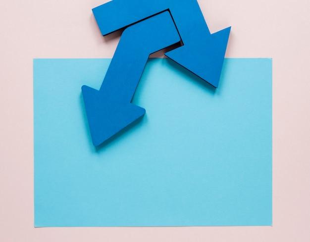 Plat lag blauwe pijlen en blauwe kartonnen mock-up op roze achtergrond