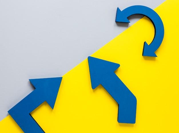 Plat lag blauwe pijlen en geel karton op witte achtergrond